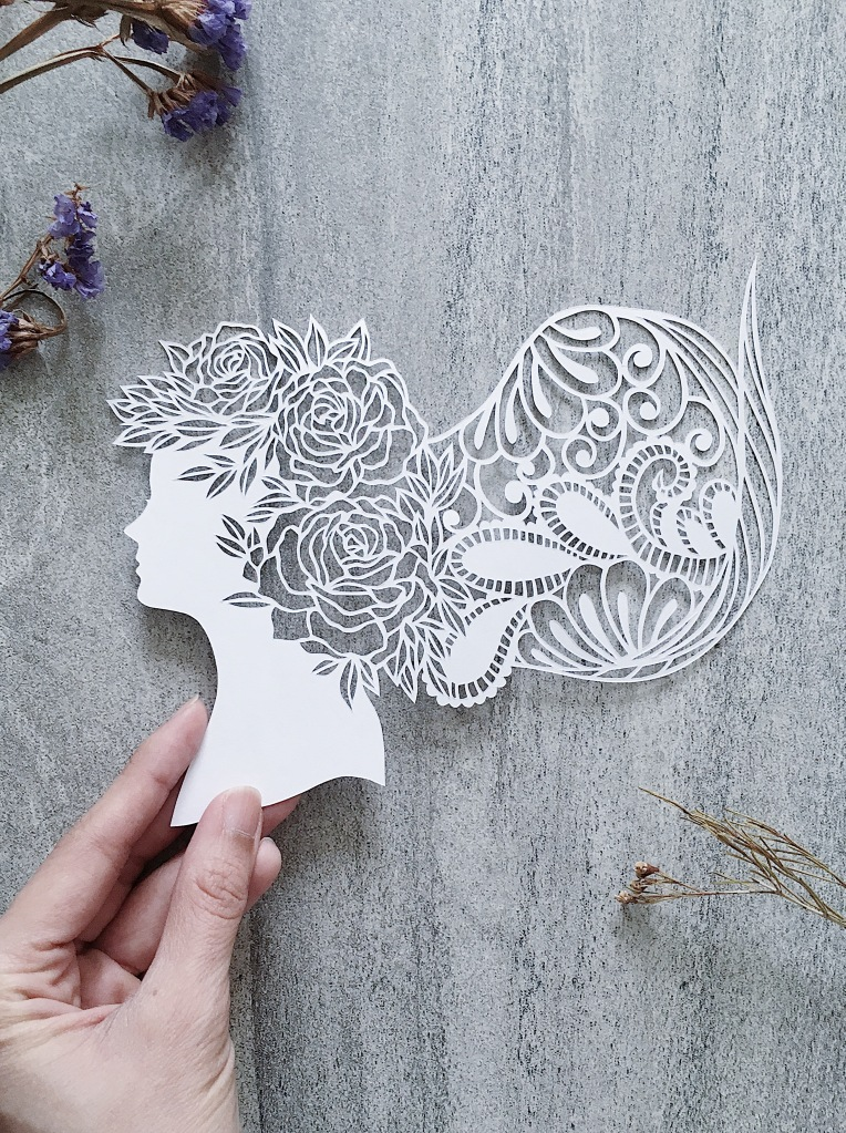 handcut paper art of a woman's silhouette decorated with florals and lace by papercut artist Yang Cuevo
