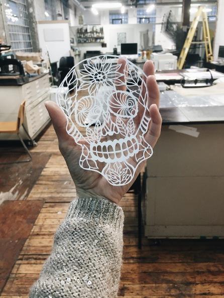 Yang Pulongbarit-Cuevo holding a handcut papercutting sugar skull artwork