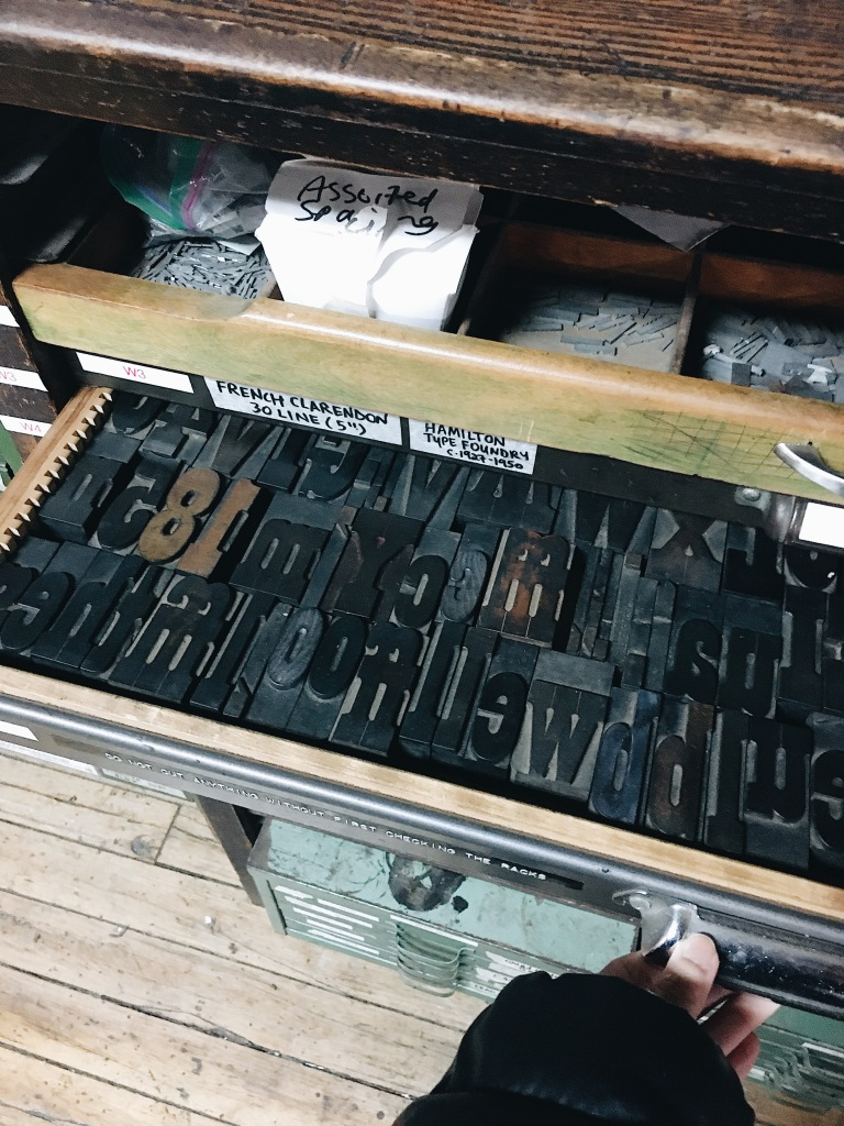 Yang Pulongbarit-Cuevo pulling out a drawer of uppercase woodblocks used for letterpress printmaking